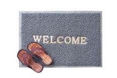 Welcome mat with brown sandals Royalty Free Stock Photos