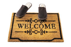 Welcome mat and slippers Stock Photo