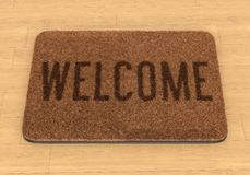 Welcome mat on wooden floor Royalty Free Stock Image