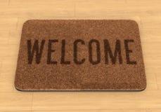 Welcome mat on wooden floor. Brown coir doormat with text Welcome on wooden floor Royalty Free Stock Image