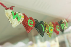 Welcome message heart alphabet hanging on mirror Royalty Free Stock Photo