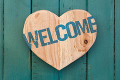 Welcome message wooden heart on turquoise painted background Royalty Free Stock Photo