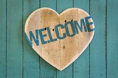 Welcome message wooden heart on turquoise painted background Royalty Free Stock Image