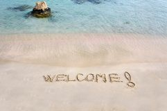 Welcome message written on white sand, with tropical sea waves in background Stock Photo