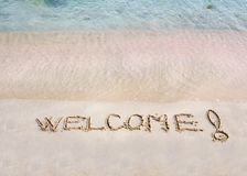 Welcome message written on white sand, with tropical sea waves in background Royalty Free Stock Photos