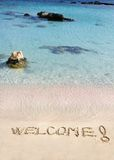 Welcome message written on white sand, with tropical sea waves in background Royalty Free Stock Image