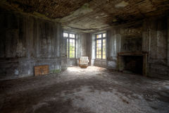 Welcome in my world of Decay. Chair with great lightning on it in an abandoned castle in France Royalty Free Stock Photography