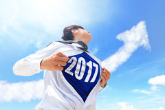 Welcome 2017 New year concept. Business man pulling his t-shirt open, showing 2017 text with a superhero suit underneath his suit Royalty Free Stock Photo