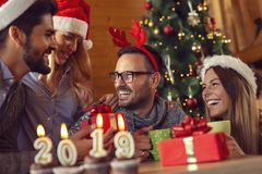 Welcome New 2019 Year. Cupcakes with lit candles shaped as numbers 2019 placed on a coffee table with group of friends celebrating and exchanging gifts in the stock photos