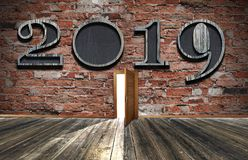 New year celebrattion concept. 2019 sign on dark brick wall. Fro. Welcome in new year 2019. wood floor and dark wooden wall room with open door. Holiday concept stock photos