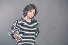 Welcome, nice to see you. Man in black and white striped sweater looking at camera with reaching out his hand offering stock photo