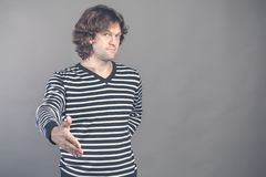 Welcome, nice to see you. Man in black and white striped sweater looking at camera with reaching out his hand offering royalty free stock photo