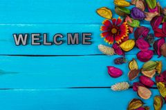 Welcome on blue wood with flower stock image