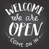 Welcome we are open chalkboard sign. Welcome we are open. A welcome sign for cafes or shop visitors on blackboard background with chalk. Hand lettering Stock Photos