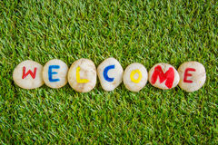 Welcome paint on stone , on the grass Stock Images