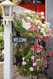 Welcome panel, black bell and flowers at hotel entrance Royalty Free Stock Photography