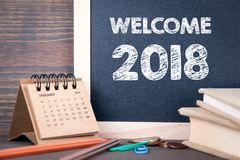 Welcome 2018. paper calendar and chalkboard on a wooden table.  Stock Photo