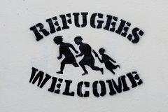 Welcome Refugees Text Stencil Print on White Wall. Welcome Refugees Text and Sign, Stencil Print on White Wall, Symbol Royalty Free Stock Image
