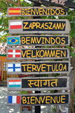 Welcome sign. Welcome in different languages on the beach stock photography