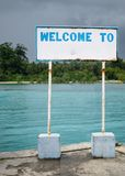 Welcome Sign Board at a Port. The water is blue and the sky is dark with clouds Stock Image