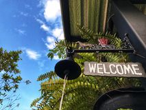 Welcome sign board and vintage bell front of shop. Fern and blue sky on the vacation Royalty Free Stock Photo