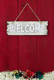 Welcome sign with Christmas garland and gifts border hanging on antique red wooden background Royalty Free Stock Images