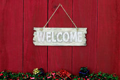 Welcome sign with Christmas garland and presents border hanging on antique red wooden background Stock Photos