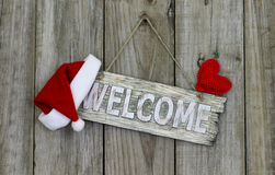 Welcome sign with Christmas Santa Claus hat and red heart hanging on rustic wooden background Royalty Free Stock Photo