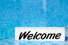 Welcome Sign And Empty Swimming Pool Surface In The Background. Pool Party Invitation Concept Royalty Free Stock Photography