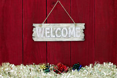 Welcome sign with garland Christmas border hanging on antique red wooden background Royalty Free Stock Images