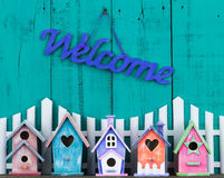 Welcome sign hanging over fence and birdhouses Royalty Free Stock Photo
