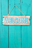 Welcome sign hanging on teal blue wood door Stock Image