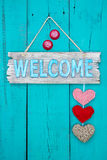 Welcome sign with hearts hanging on rustic door Stock Photos
