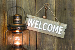 Welcome sign with iron key hanging next to antique lantern Stock Photos