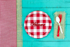 Welcome sign with picnic concept. Welcome sign with red and white checkered plate and gingham and burlap border on antique teal blue wood background; above view Stock Photos