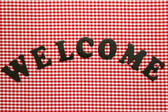 Welcome sign on red checkered (gingham) tablecloth. Welcome sign on red checkered (plaid) tablecloth Royalty Free Stock Photos