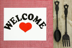Welcome sign on red checkered tablecloth with cast iron spoon and fork Royalty Free Stock Photography