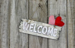 Welcome sign with red hearts hanging on rustic fence. Welcome sign with red hearts hanging on shabby wooden background royalty free stock photo