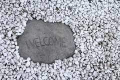 Welcome sign rock surrounded by white rocks. A large stone welcome sign surrounded by little white rocks stock images