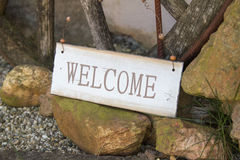 Welcome sign at the side of a foot path. Welcome sign balanced on rocks at the side of a foot path in the garden to greet guests as they enter the property Stock Photo