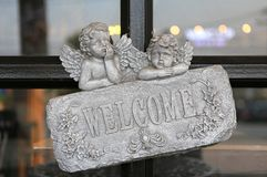 Welcome sign on stone against glass door of restaurant.  royalty free stock photography