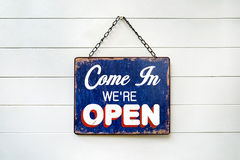 Welcome Sign with text & x22;COME IN WE& x27;RE OPEN& x27; hanging on wood white wall. Business sign that says 'Come in we're open' hanging on Royalty Free Stock Images