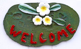 Welcome sign on the white background wall Stock Photo