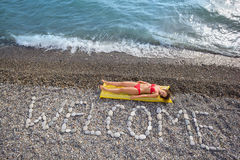 WELCOME at stony coast, woman on mattress Stock Images
