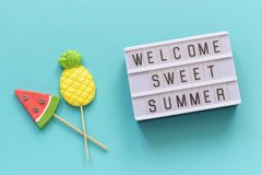 Welcome Sweet Summer Text On Light Box, Pineapple And Watermelon Lollipops On Stick On Blue Background. Concept Hello Royalty Free Stock Photography