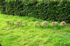 Welcome. Text symbol on green grass in garden Royalty Free Stock Photo