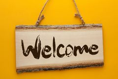 Welcome Text On Wooden Sign. The word `Welcome` on a wooden sign hanging on a rope on a yellow background stock photo