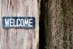 Welcome text on wooden tag hanging on wooden wall royalty free stock images