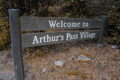 Welcome to Arthur`s Pass Village sign, wooden street sign, in Arthur`s Pass, Canterbury, New Zealand stock photos