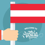 Welcome to Austria card with male hand holding Austrian flag. Stock Photos